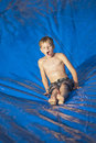 Young boy sliding down a slip and slide outdoors Royalty Free Stock Photo