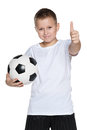 Young boy with soccer ball holds his thumb up on the white background Stock Photo