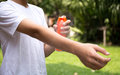 Young boy spraying insect repellents on skin with spray bottle Royalty Free Stock Photo