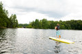 Young boy stand up paddle boarding wearing a life jacket on a lake Royalty Free Stock Photo