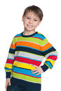 Young boy in a striped sweater stands on the white background Stock Photo