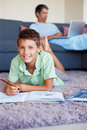 Young boy studying on floor with father behind him Royalty Free Stock Photography