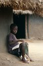 A young boy studying outside his hut, Uganda. Stock Photography