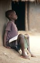 A young boy studying outside his hut, Uganda. Stock Images