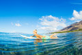 Young boy surfing paddling out to waves Royalty Free Stock Photo
