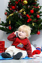 Young boy talking on mobile phone under a christmas tree. Royalty Free Stock Photo