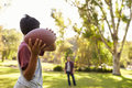 Young boy throwing ball to dad in park, focus on foreground Royalty Free Stock Photo