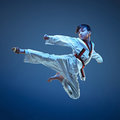 Young boy training karate on blue background Royalty Free Stock Photo