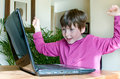 Young boy victorious with laptop Stock Photo