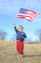 Young boy waving the american flag holding a united states over his head and smiling Royalty Free Stock Image