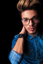Young boy wearing glasses and denim shirt in dark studio Royalty Free Stock Photo