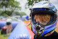 Young boy wearing a motorcycle helmet at county fairground waiting to go on quad bike safety concept Stock Images