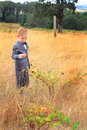 Young boy wearing a suit in tall grass kindergartner walking country field of and bow tie picking blackberries Stock Image