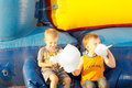 Young boys happily sharing a large cotton candy ball sitting near colorful inflatable bouncer amusement Royalty Free Stock Photo