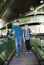 Young boys on a moving staircase at the airport Stock Photos