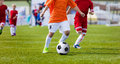Young boys playing football soccer game on sports field running players in sport shirts kids and kicking Stock Photos