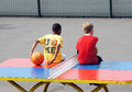 Young boys sit on a table tennis table boy with basketball sits in the playground of clissold park london Royalty Free Stock Image