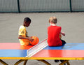 Young boys sit on a table tennis table boy with basketball sits in the playground of clissold park london Stock Images