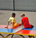 Young boys sit on a table tennis table boy with basketball sits in the playground of clissold park london Stock Photos