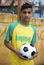 Young brazilian football player holding soccer ball portrait of in brasil shirt outdoors Royalty Free Stock Photos