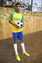 Young brazilian football player holds soccer ball portrait of in brasil shirt holding outdoors on a dirt pitch Stock Image