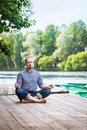Young breaded man with closed eyes relaxing and meditaing in summer morning attractive sitting on wooden pier Royalty Free Stock Photo