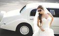 Young bride against limo hot summer day wedding picture Royalty Free Stock Images