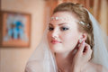 Young bride the beautiful checks a make up and jewelry looking in a mirror Royalty Free Stock Photos