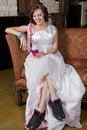 Young bride on couch wearing tennis shoes brunette a bridal gown and Royalty Free Stock Image