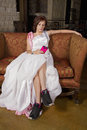 Young bride on couch wearing tennis shoes brunette a bridal gown and Royalty Free Stock Images