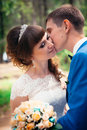 Young bride and groom kissing on the background of the forest the road Royalty Free Stock Photo