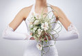 A young bride holding a beautiful bouquet of flowers in white dress the image is taken on grey background Royalty Free Stock Photo