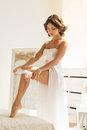 Young bride putting garter on her leg Royalty Free Stock Photo