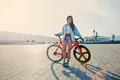 Young brown haired woman standing with her modern pink bicycle at sunset Royalty Free Stock Photo