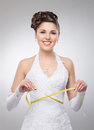 A young brunette bride posing in a white dress with a tape and happy caucasian and holding measuring the image is taken on light Royalty Free Stock Images