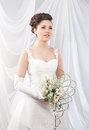 A young brunette bride in white clothes holding flowers and attractive caucasian and bouquet of the image is taken on light Royalty Free Stock Photography