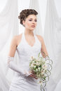 A young brunette bride in white clothes holding flowers and attractive caucasian and bouquet of the image is taken on light Royalty Free Stock Photo