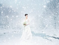 A young brunette bride in a white dress on the snow beautiful and emotional with beautiful flowers image is taken beautiful and Royalty Free Stock Image