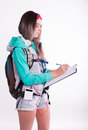 Young brunette female student standing and listening to music from your device. Royalty Free Stock Photo