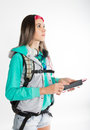 Young brunette female student standing looks into the distance and holding your smartphone beautiful backpacker Royalty Free Stock Images