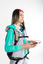 Young brunette female student standing looks into the distance and holding your smartphone beautiful backpacker Stock Image