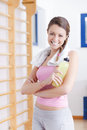 Young brunette fitness woman with towel and bottle portrait of gym Royalty Free Stock Photos