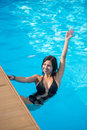 Young brunette girl with a beautiful smile in a swimming pool holding on to a broadside of pool Royalty Free Stock Photo