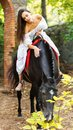 A young brunette girl sits on a horse and strokes it. In the park. Royalty Free Stock Photo