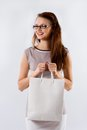 Young brunette girl holding shopping white bag smiling woman in glasses with on a background Royalty Free Stock Photo