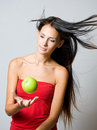 Young brunette juggling fresh apple. Stock Image