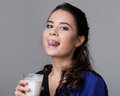 Young brunette licking milk from a goblet in black and blue shirt close up Royalty Free Stock Photo