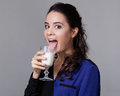 Young brunette licking milk from a goblet in black and blue shirt half turned Stock Images