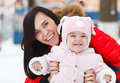 Young brunette mother with her daughter outdoors winter Stock Photos