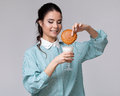 Young brunette wetting a cookie in a glass of milk blue shirt isolated on white background Royalty Free Stock Photography